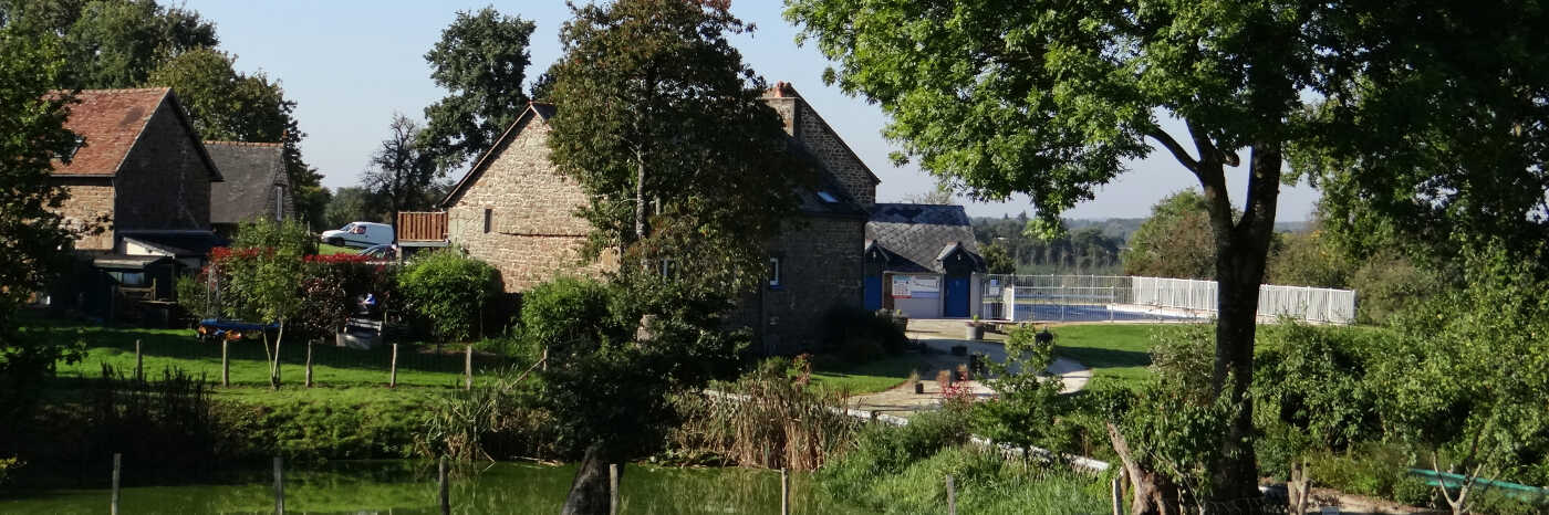 Photo of Parc Mayenne from a distance across a pond, 4 buildings and the parc pool are visible