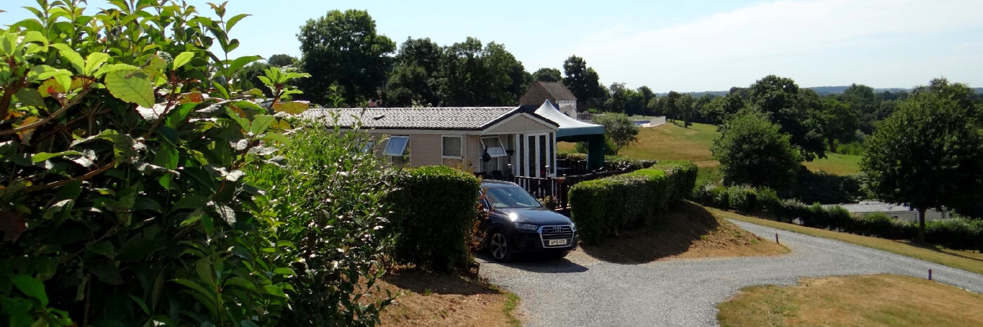 photo of a holiday home sited on Parc Mayenne surrounded by a neatly trimmed hedge with a car in the driveway