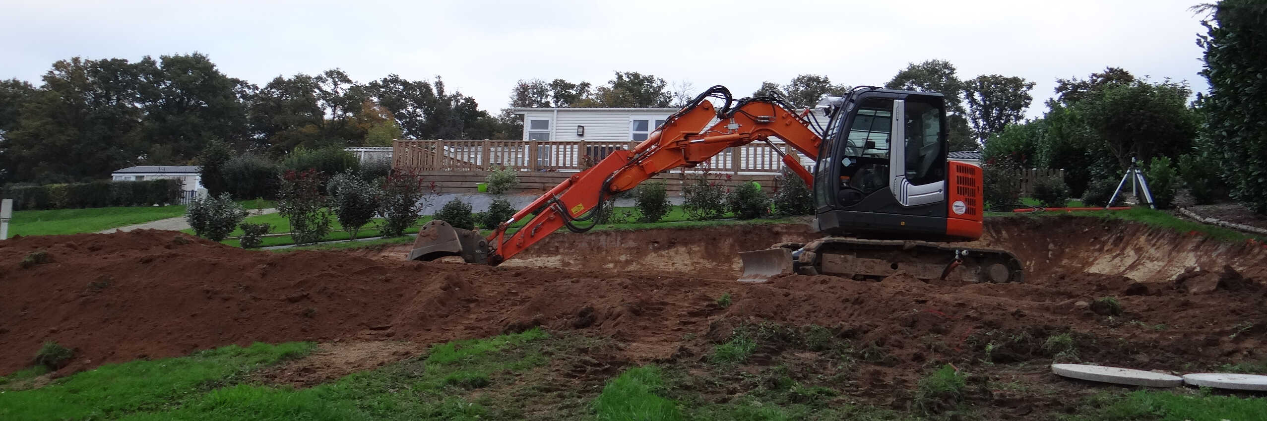 Photo of an orange digger moving earth in front of some park homes at Parc Mayenne.