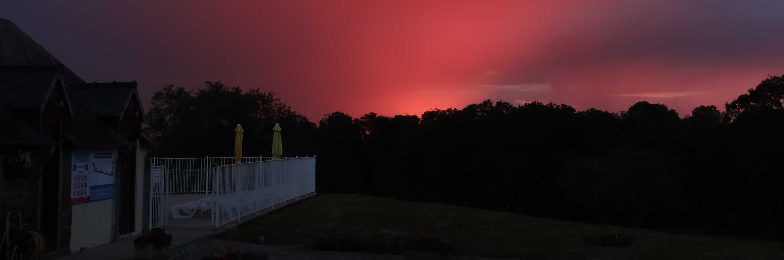 Photo of a bright red sunset creating a silhouette of trees, to the left is Parc Mayenne's swimming pool.