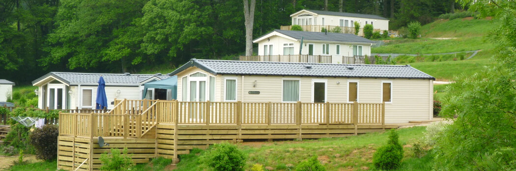 Photo of some park homes with decking sited on a hill at Parc Mayenne.