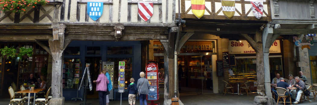 Photo of shops and restaurants in old, French buildings, flags of French crests hanging from them.