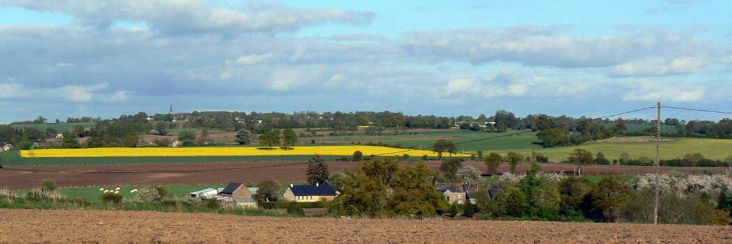 Photo of a view across the countryside, a small farm complex sits among fields of green, brown and yellow.
